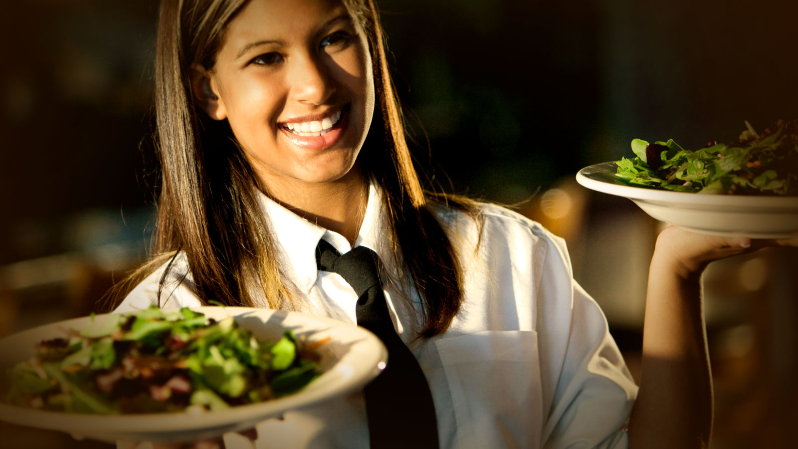 A waitress holds two plates of salad.